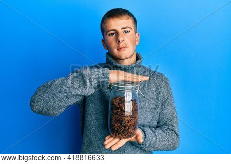 Young caucasian man holding jar of raisins relaxed with serious expression on face. simple and natural looking at the camera.