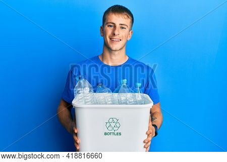 Young caucasian man holding recycling wastebasket with plastic bottles smiling and laughing hard out loud because funny crazy joke.