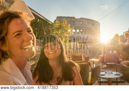 Two Smiling Women At Sunset In Rome, Italy. Happy Hour. Colosseum In Background High Quality Photo