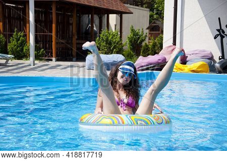 Happy Woman In Plastic Hat Swimming In Pool Water On Colorful Inflatable Ring. Having Fun. Summer Va