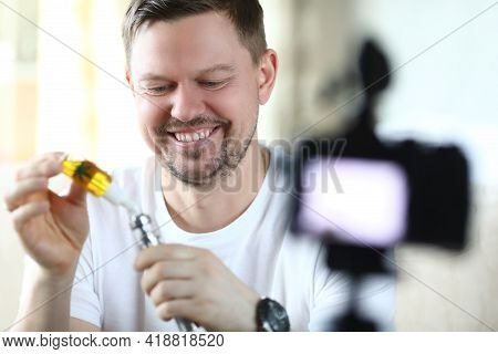Smiling Man Fills Marijuana Vaporizer For Smoking And Takes Pictures