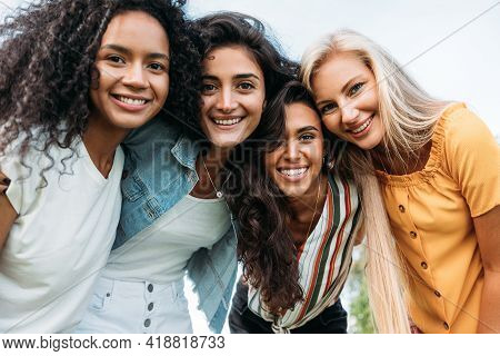 Group Of Happy Young Women Standing Together And Looking At Camera