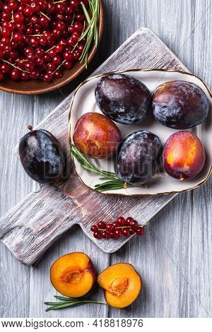 Fresh Sweet Plum Fruits Whole And Sliced In Plate With Rosemary Leaves On Old Cutting Board With Red