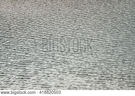 Monochrome Texture Of Silver Calm Water Of Lake. Meditative Ripples On Water Surface. Nature Minimal