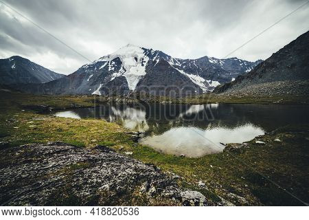 Scenic Mountain Landscape With Glacial Lake Among Mountains And Glacier Under Gray Cloudy Sky. Atmos