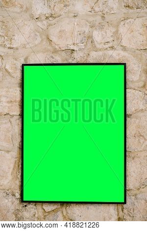 Blank Vertical Painting In Black Frame On Masonry Background