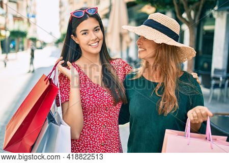 Beautiful hispanic mother and daughter smiling happy and shopping at the city.