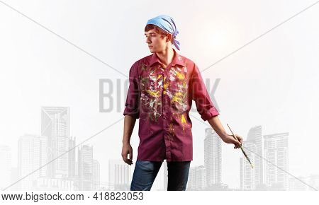 Young Artist Posing With Paintbrush. Painter In Dirty Shirt And Bandana Standing On Background Moder