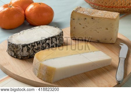 Cheese platter with different types of cheese, Double Dutch cheese, Monte Enebro from Spain and Taleggio tartufo from Italy close up as a snack or appetizer