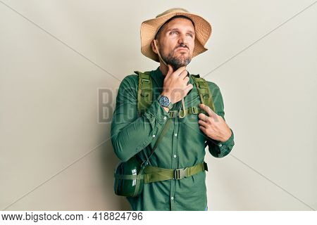 Handsome man with beard wearing explorer hat and backpack touching painful neck, sore throat for flu, clod and infection