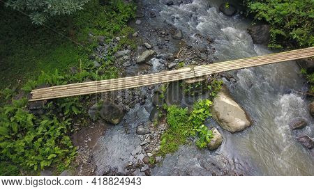 Aerial View To Bamboo Footbridge Over The River. Bamboo Bridge Across A Creek In A Natural Forest Tr