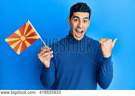Handsome hispanic man holding macedonian flag pointing thumb up to the side smiling happy with open mouth