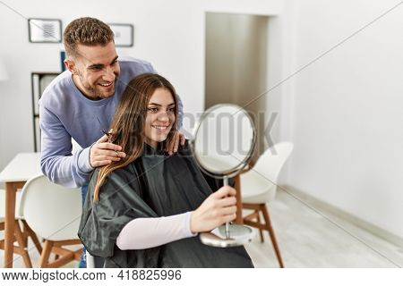 Young man cutting hair his girlfriend at home.