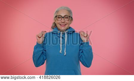 Elderly Gray-haired Woman Granny In Casual Blue Hoodie Celebrate Success Win Scream Rejoices Doing W