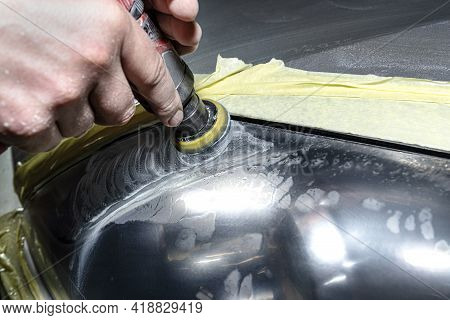 A Car Sprayer Polishes The Headlamp With A Small Pneumatic Sponge Grinder.
