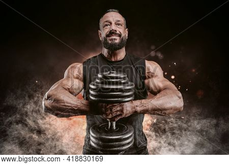Muscular Man Posing With A Dumbbell On A Background Of Fire And Smoke. Fitness And Bodybuilding Conc