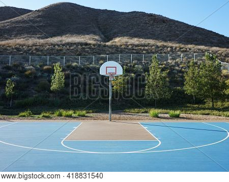 Half Court View Of Public Basketball Court With Hills In Background