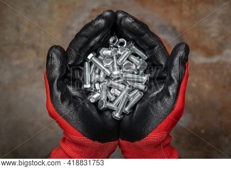 Person wearing protective gloves holding a handful of bolts and nuts in cupped hands against rusty metal background