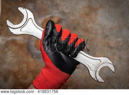 Person wearing protective glove holding big wrench against rusty metal background