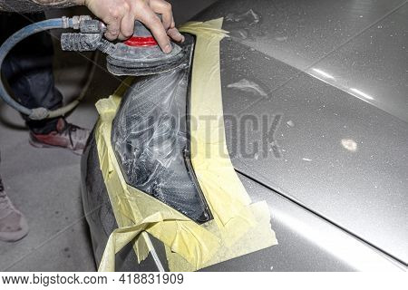 A Car Sprayer Polishes The Headlamp With A Pneumatic Sponge Grinder.