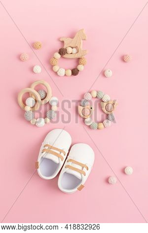 Baby Shoes And Teethers On Pink Background. Organic Newborn Fashion, Branding, Small Business Idea