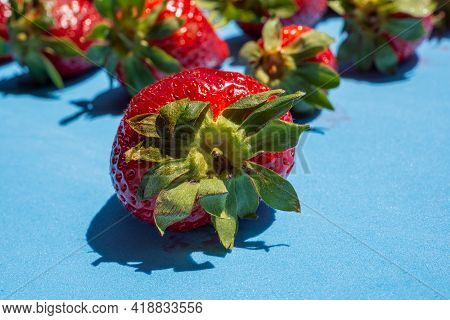 Ripe Red Strawberry With Green Leaves On Blue Background.healthy Food Concept