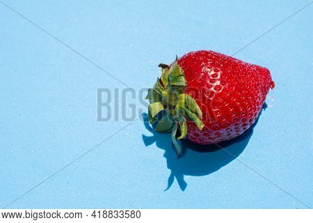 Ripe Red Succulent Strawberry Ready To Eat Isolated On Blue Background Illuminated By Sunlight.healt