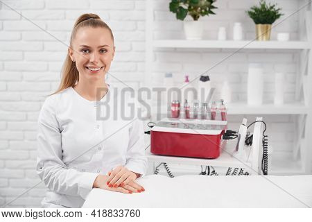 Front View Of Smiling Beautiful Woman In White Uniform Sitting In Clinic Near Special Preparation Fo