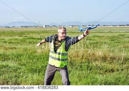 Abakan, Russia - August 08, 2020: A Man In Uniform Playing With A Toy Plane At The Airport.