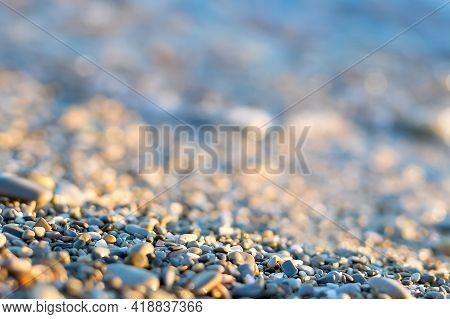 Close-up And Soft Focus Of The Pebbles On The Seashore Against The Rolling Waves In The Evening Suns