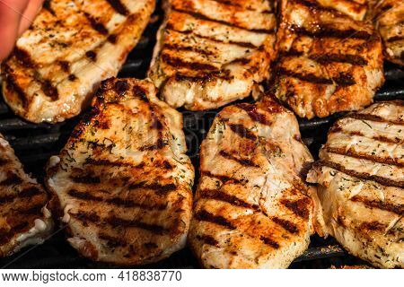 Grilling Pork Steaks. Delicious Meat Steaks Close Up Cooking On The Barbecue Grill