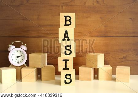 Five Wooden Cubes Stacked Vertically To Form The Word Basis On A Brown Background. Cubes Are Scatter