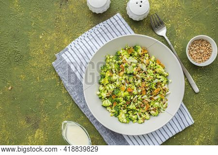 A Healthy Salad Of Raw Broccoli, Onions, Raisins And Fried Sunflower Seeds With Yoghurt Dressing In