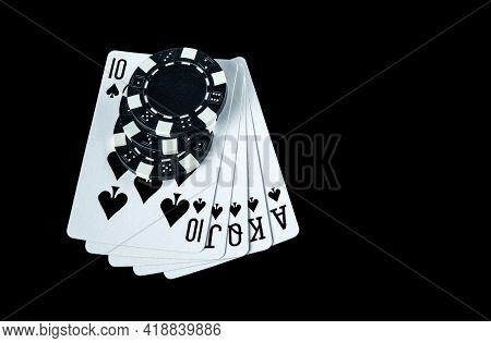 Poker Game With Royal Flush Combination. Chips And Cards On The Black Table In Poker Club. Free Adve