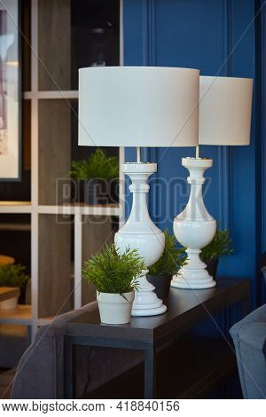 Interior Decor. Two Large White Table Lamps With Large Shades In A Dark Interior. Vertical.