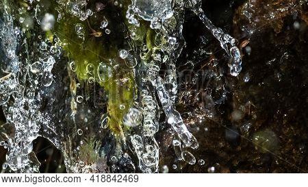 Nature Abstract: Splashing Water Streaming Down And Enveloping Fresh Green Vegetation