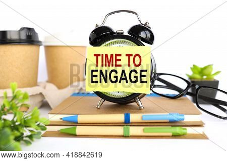 Time To Engage. There Is A Sticker On The Alarm Clock. Against The Background Of A Paper Cup With Co