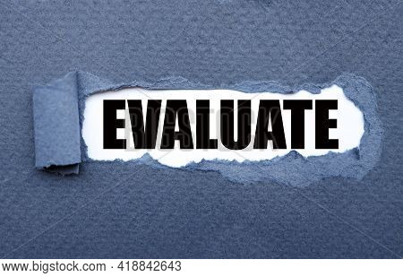 Evaluation. Text Inside Torn Blue Paper. White Sheet With Black Font.
