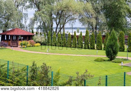 Freshly Mowed Rows Of Green Lawn At Country Residence With Summerhouse. Fence Hedge Of Fresh Thuja C