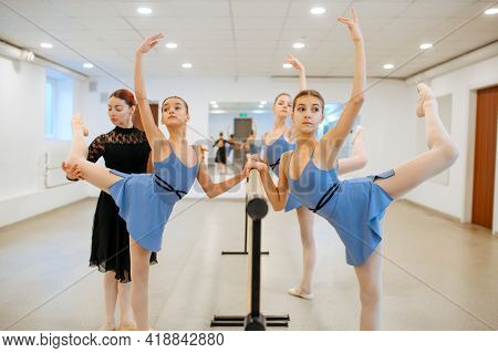 Teacher and ballerinas, exercise at barre in class