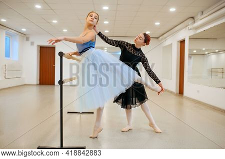 Master rehearsing with young ballerina in class