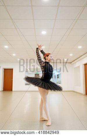 Ballerina poses at barre in class, ballet school