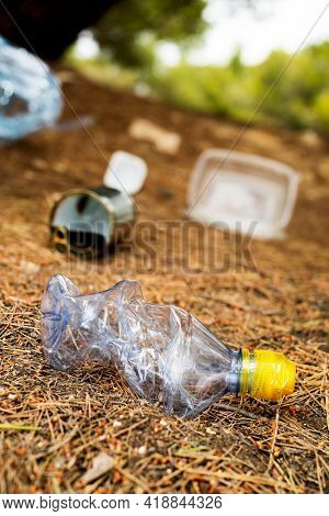 closeup of a used plastic bottle and some other garbage, such as used food cans and plastic containers, thrown on the ground of a forest