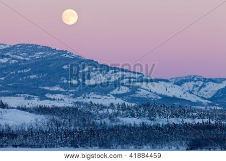 Yukon Canada winter landscape and full moon rising