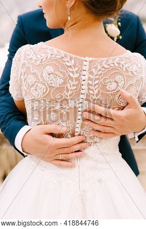 The Bride And Groom Are Standing And Hugging, Hands Of The Groom On Brides Back, Close-up