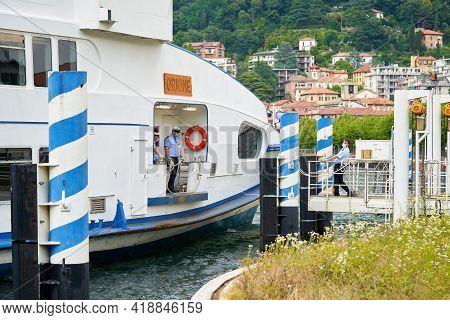 Ship Docking In The Harbor, Como Lake District. Seaman Docking Ship To The Land. Como, Italy - June