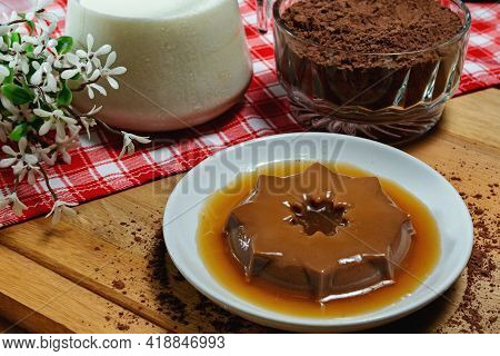 Chocolate Pudding On Porcelain Plate. Milk Jar And Glass Jar With Chocolate In Po. Wooden Base With