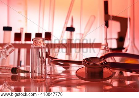 Chemical Table With Lab Glassware And Stethoscope In Red Colors. Test Tubes, Liquid Flasks, Medical