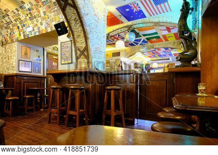 Lisbon, Portugal - January 7, 2020 : The Inside Of A Pub With Empty Chairs And Flags As A Decoration