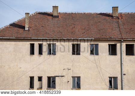 Facade Of A Residential Building, Abandoned, In Decay, With Plenty Of Windows With Broken Glass, Due